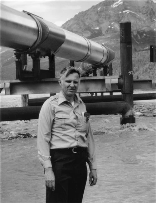 Professor Emeritus William J. Hall posing before the Alaska Pipeline, one of the projects on which he worked.
